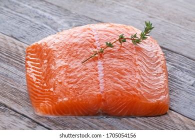 Fresh salmon filet with thyme sprig on a vintage wooden board