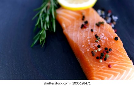 Fresh salmon fillet with aromatic herbs, spices and vegetables, healthy food, diet or cooking concept. Close up view.