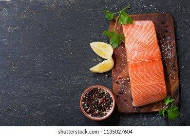 fresh salmon fillet with ingredients for cooking on a wooden board, top view
