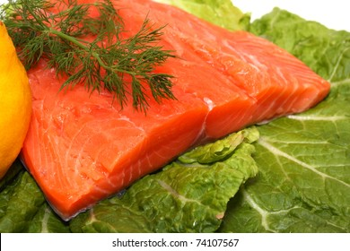 Fresh salmon fillet with lemon and dill on lettuce leaves
