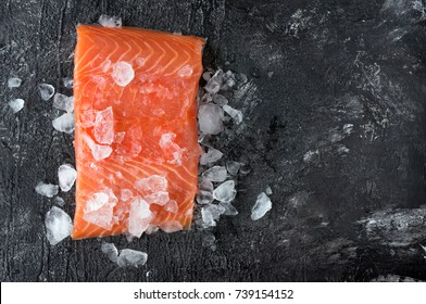 Fresh salmon fillet on ice with copy space. Dark slate background. Top view.