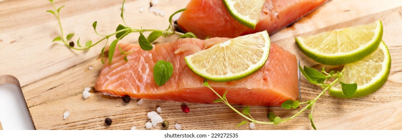 Fresh salmon fillet with oregano and lime slices. Selective focus. Panoramic image.