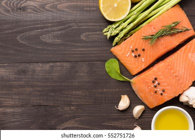 Fresh salmon fillet with spice on wooden background. Copyspace for your text.