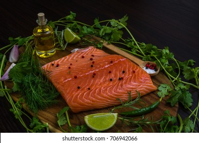 Fresh salmon fillet with vegetables, herbs, spices on chopping board over rustic wooden background, top view