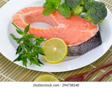 fresh salmon fillet with vegetables and lemon slices.