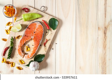 Fresh salmon and fish oil capsules on wooden background full of vegetable