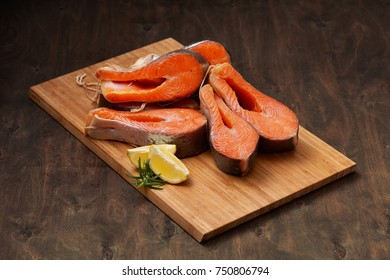 Fresh salmon fish steaks on the wooden cutting board with lemon and greens
