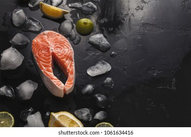 Fresh salmon with ice and lemon slices on dark background. Organic cooking ingredients for seafood restaurant, copy space