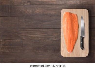 Fresh salmon and knife on cutting board on the wooden table. Top view.