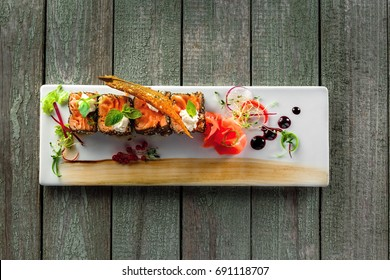 Fresh salmon rolls with pickled ginger and soy sauce. Healthy Japanese food made of salmon fish on a table. Traditional sashimi meal. Top view.