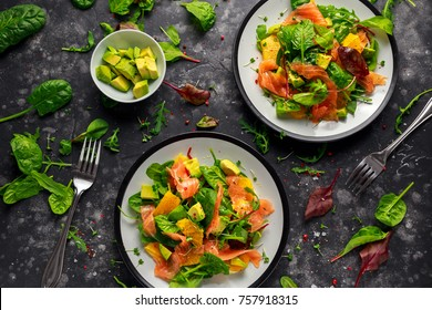 Fresh salmon salad with avocado, orange and green vegetables.