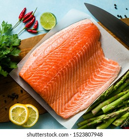 fresh salmon slice on a wooden cutting board with fresh aromatic herbs and asparagus on the table. cooking recipe. food background. fresh fish products