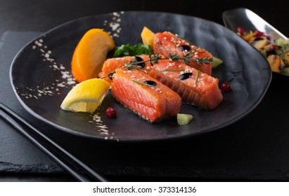 Fresh salmon with spices, herbs, rosemary and lemon on a plate
