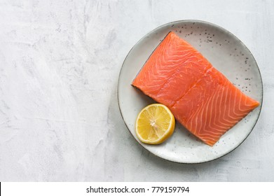 Fresh salmon steak with lemon on rustic plate. Top view. Concrete background with copy space.
