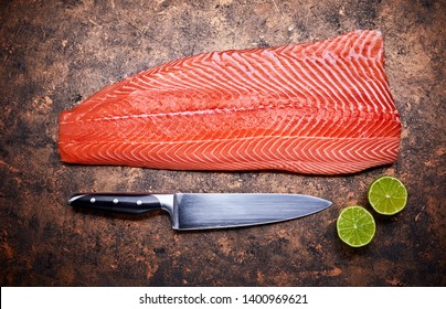 Fresh salmon steak red fish on grunge background with knife and cuted lime top view.