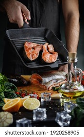 Fresh salmon steaks in a frying pan. The chef uses a knife to cut the salmon into steaks.