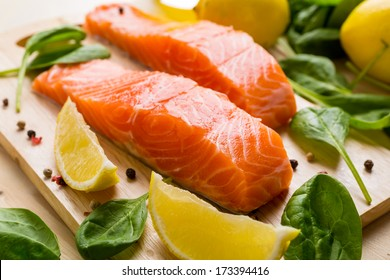 Fresh Salmon Steaks with Lemons and Baby  Spinach  on a Cutting Board