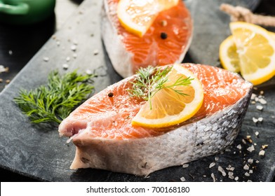 Fresh salmon steaks on ice with lemon and herbs on dark background