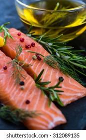 fresh salmon steaks on slate board, with olive oil