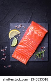 Fresh salmon or trout steak on slate board on black textured background. Top view. Flat lay. Ingredients for cooking. Healthy eating.Vertical image.
