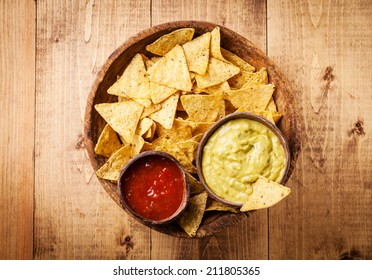 Fresh salsa and guacamole dips with nachos chips on wooden background