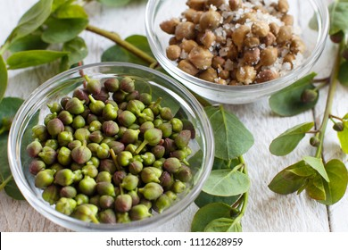 Fresh and salted capers in bowls close up