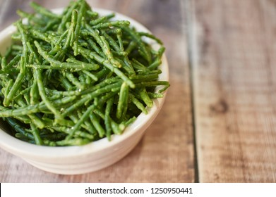 Fresh samphire in a white bowl on an old wooden worktop