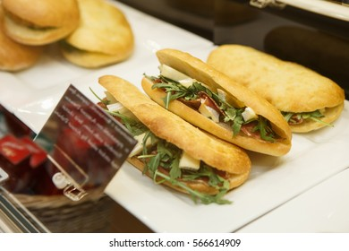 Fresh sand wich with vegetable leaves,ham slice on sale in cafe under window case.Sandwiches in restaurant.Fresh fast food dish close up.Enjoy tasty snacks for lunch