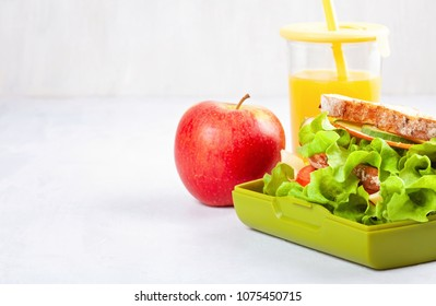 Fresh sandwich, apple and orange juice for healthy lunch of a kid or a student in the plastic lunch box