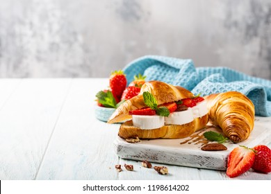 Fresh sandwich with croissant with goat cheese, strawberries, honey and pecans on wooden cutting board with copy space.