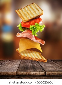 Fresh sandwich with flying ingredients placed on wooden planks. Copyspace for text, high resolution image