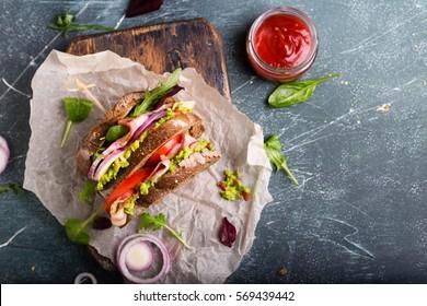 Fresh sandwich with guacamole, tomatoes, arugula and bacon
