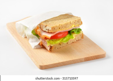 fresh sandwich with ham, cheese and vegetables in paper bag