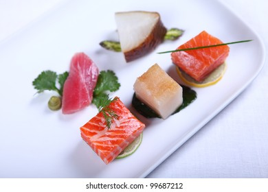 Fresh sashimi decorated with greens and lime. Close-up