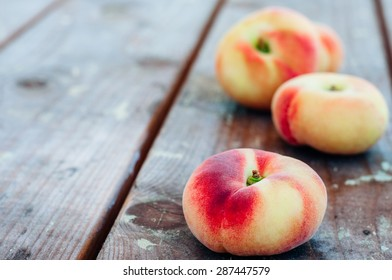 Fresh Saturn peaches on old wooden board background