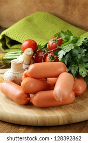 fresh sausages and parsley on wooden cutting board