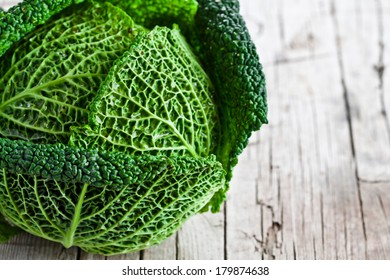 fresh savoy cabbage closeup on rustic wooden background