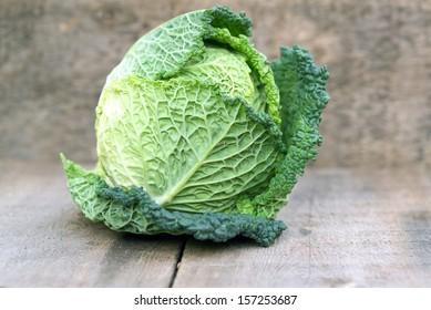 Fresh Savoy Cabbage on wooden background