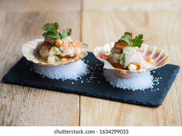 Fresh Scallops Ceviche served in a shell are shown on a table at a restaurant