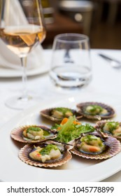 Fresh scallops in the shell served in a fancy restaurant with a glass of rose wine. Seafood starter creatively arranged on a white restaurant plate. Shellfish