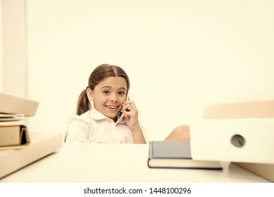 Fresh school gossip. She like talking too much. Discussing rumors. Cute gossip girl. Schoolgirl smiling face discuss fresh gossips with mates. Child use smartphone mobile to communicate in school.