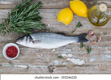 Fresh sea bass with lemon, rosemary, garlic, olive oil and pink pepper on wooden boards