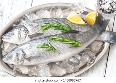 Fresh sea bass with rosemary and lime wedges on the metal tray