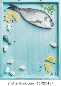 Fresh Sea bream or dorado raw uncooked fish with seasoning and lemon slices over turquoise blue tray background, top view, copy space