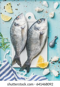 Fresh Sea bream or dorado raw uncooked fish with seasoning over turquoise blue background, top view