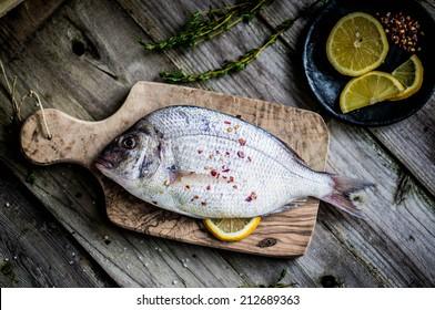 Fresh sea bream on wooden board