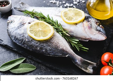 Fresh sea fish with olive oil, spices and lemon ready for cooking on slate. Dorado or sea bream fish. Horizontal. Closeup view