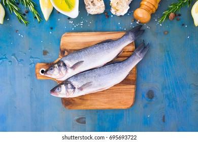 fresh sea fish preparation - top view of two raw seabass fish on cutting board