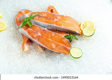 fresh sea ocean red fish is cut into pieces, lies on ice, without a head, cherry, slices of lemon and lime are cut round, lie around, with basil, light, top view from the side