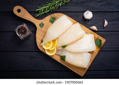 Fresh seafood background .  Squid tubes with lemon
